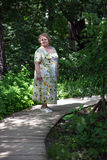 Old lady walking in garden Royalty Free Stock Image