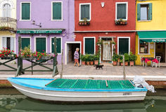 An old lady walks with her cat in Burano, Italy Stock Image