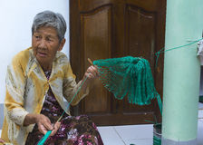 Old lady weaves fishing net in front of her home. Stock Photo