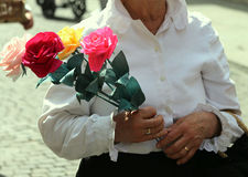 old lady with white blouse walks with a pack of four roses Stock Photos