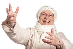 Old lady at winter with open arms smiling. Old lady in warm clothes at wintertime, arms open, smiling Stock Photo