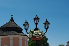An old lamp against a blue sky. Flowers. Stock Images
