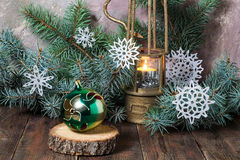 Old lamp with burning candle, Christmas ball and Christmas tree Royalty Free Stock Photo