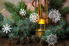 Old lamp with burning candle in Christmas tree branches Stock Images