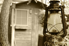 Old lamp in the door of a wooden hut Stock Photography
