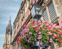 Old lamp with flowers and Delft cathedral Royalty Free Stock Photos