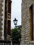 Old lamp hanging between ancient brick palace building in Great Britain Royalty Free Stock Images