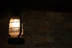Old lamp hanging in dark room with brick wall behind Royalty Free Stock Photos