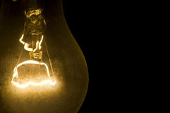 Old lamp with an incandescence thread on a black Stock Image