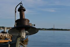 Old lamp for night deep-sea fishing installed on fisherman boat. Boat is tied with a ropes to molo. There is red buoy visible on the water in background. There Stock Images