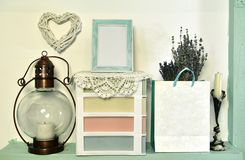 Old lamp, picture frame with blank, paper bag with lavender bunch and box on shelf stock photos