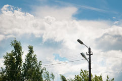 Old lamp post, tree foliage and blue sky with clouds. Day Royalty Free Stock Photo