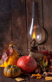 Old lamp with pumpkins, acorns and leaves. Still life with vintage burning lamp with colorful pumpkins, acorns and autumn leaves on old wooden table Royalty Free Stock Photo
