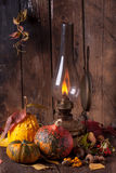 Old lamp with pumpkins, acorns and leaves. Still life with vintage burning lamp with colorful pumpkins, acorns and autumn leaves on old wooden table Royalty Free Stock Images