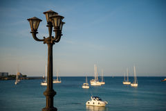 Old lamp in quiet harbor Stock Photography