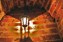 Old lamp on the red bricks wall. Vintage style lamp on the red bricks arch wall Stock Photos