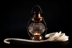 Old lamp and rope. On black background Royalty Free Stock Photo