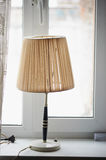 Old lamp with shade on an  window in a village house. Stock Photo