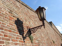 Old lamp with a shadow on the wall. An old street lamp with a shadow on the wall, blue sky in background, sunny day Royalty Free Stock Image