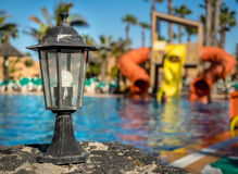 Old lamp and slides at the Resort pool Royalty Free Stock Photography