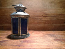 Old lamp on a table. An old lamp on a wooden table Royalty Free Stock Photo