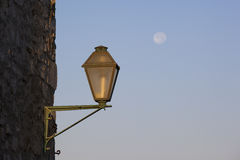 An old lamp on a wall, with a full moon in background Stock Photos