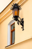 Old lamp with windows on wall. Fragment of the wall with the window and the old iron street lamp Stock Photo