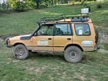 Old Landrover in rally version. Vintage yellow muddy four wheel drive Landrover in rally version parked on grass. Left side view, roof trunk stock photo