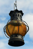 Old lantern. An old oil lantern shown toward a blue clouded sky Royalty Free Stock Photos