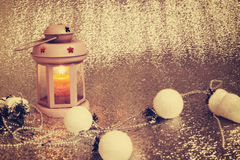 Old lantern with burning candle stands on silver background Royalty Free Stock Images