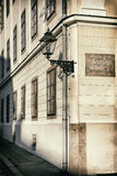 Old lantern at the corner of the street. Vintage style photo of an old lantern at the corner of the street. The street sign in old croatian and german laguages Royalty Free Stock Photos