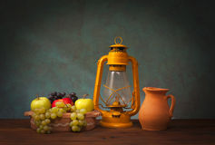 Old lantern and fruits. On vooden table Stock Photo