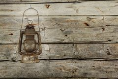 Old lantern. Hanging on a wooden barn wall Stock Photos
