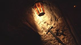 An old lantern hangs on a brick wall and illuminates a miner's mining pick, background