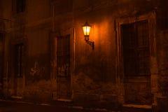 Old lantern illuminating a dark street stock photo