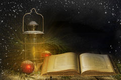 Old Lantern Open Book. An old lantern casting warm light on an old open book resting on wood surface with pine boughs, red Christmas ornaments and snow falling Royalty Free Stock Images