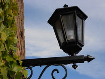 Old lantern. Photography of old lantern on brick wall with green leaves and blue skies on background, summer day Stock Photography