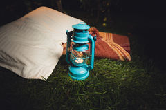 Old lantern, pillow and blanket lying on grass at night Royalty Free Stock Photos