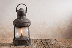 Old lantern on wood. Old kerosene lantern on old wood with grunge wall Royalty Free Stock Photos