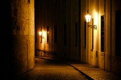 Old lanterns illuminating a dark alleyway medieval street at night in Prague, Czech Republic. Low key photo with brown yellow tones from the lanterns as single royalty free stock image
