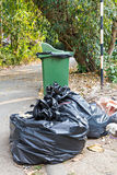 Old large green wheel bin and pile of garbage bags Royalty Free Stock Photography