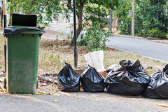 Old large green wheel bin and pile of garbage bags Stock Images