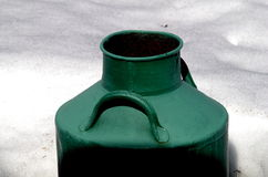 Old large milk can painted in green color in the snow Royalty Free Stock Photos