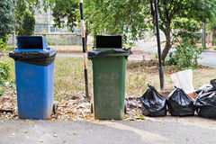 Old large wheel bins and pile of garbage bags Royalty Free Stock Images