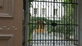 Old Latticed Gate. Zooming through a barred gate at the entry of an old court stock video