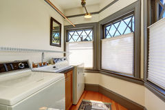 Old laundry room interior with white appliances and vintage windows. Stock Photo