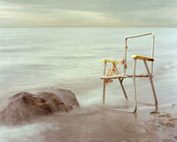Old lawn chair and rock by water. Royalty Free Stock Photography