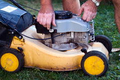 Old lawnmower. A man checking a lawnmower Royalty Free Stock Photo