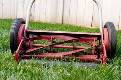 Old lawnmower closeup. Old reel lawnmower on lush green lawn royalty free stock image