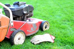 Old lawnmower and gloves Royalty Free Stock Image